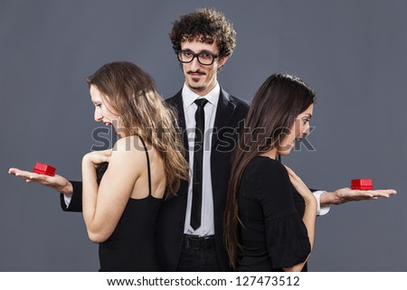 Boy giving the same gift to his two unaware girlfriends - stock photo
