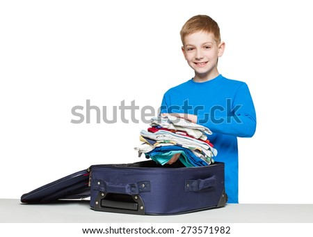 Boy going travelling packing luggage bag with clothes