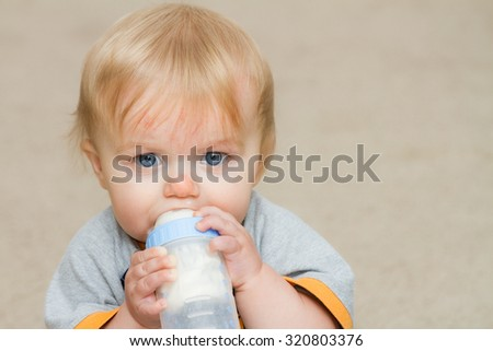 Boy grasping his bottle while looking at the camera