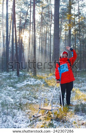 Boy greets someone in the middle of wood in winter time - stock photo