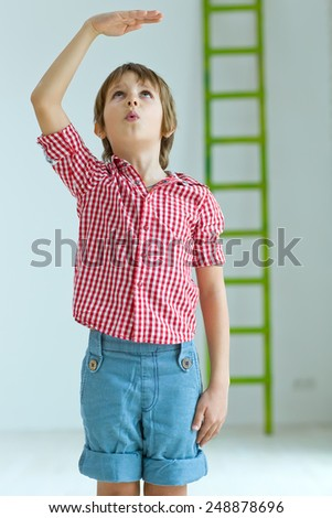 Boy growing tall and measuring himself  - stock photo
