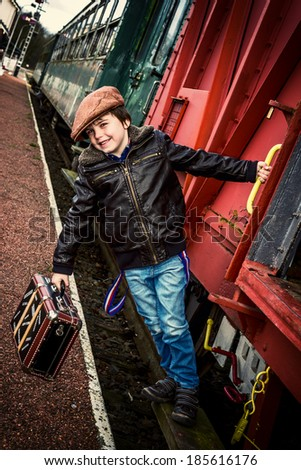boy hanging on the side of a train, instagram style effect added