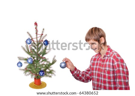 boy hangs the last ornament on his christmas tree isolated on white