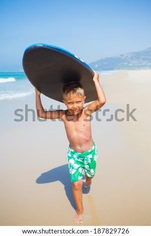 Boy has fun on the surfboard in transparency sea - stock photo