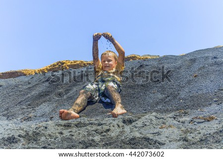 boy has fun playing with the black sand of the volcanic beach