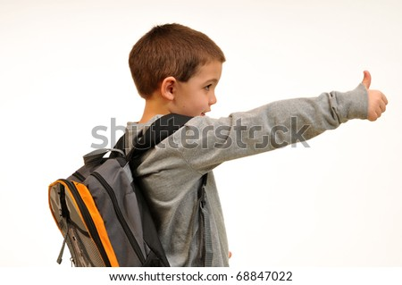 Boy has his backpack on and gives the thumbs up, ready for school. - stock photo