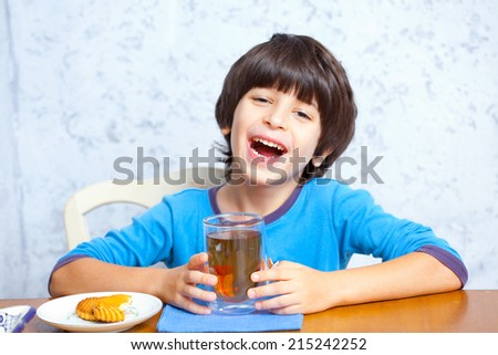 boy having fun laughing with a drink in hand. cheerful breakfast - stock photo
