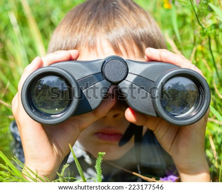 Boy hiding in grass looking through binoculars outdoor - stock photo