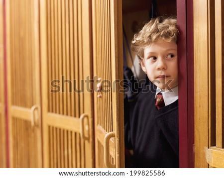 Boy hiding in locker - stock photo