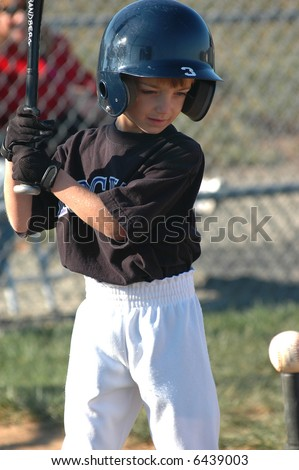Boy hitting Baseball Off Tee