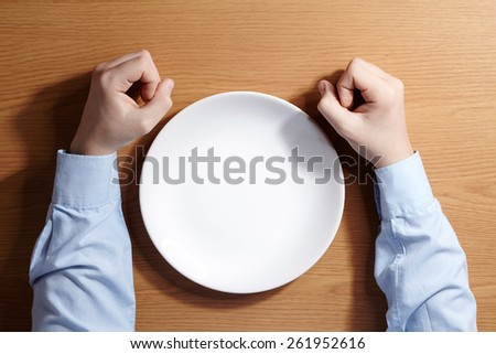 Boy holding a fists sitting at the table with white plate. Top view. - stock photo
