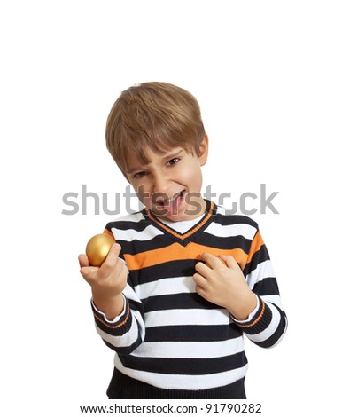 boy holding a golden egg, isolated on white background - stock photo
