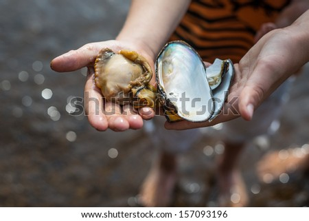 Boy holding a huge chunk of meat from a fresh water clam found in a Swedish lake.
