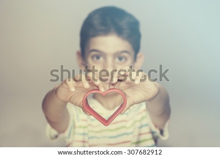 Boy holding a red heart. Cross processed image for vintage look - stock photo