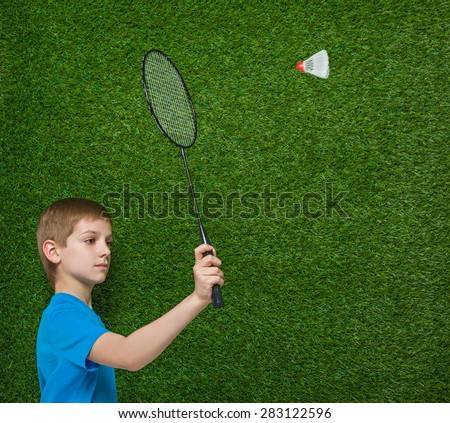 Boy holding badminton racket flying shuttlecock