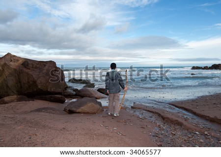 boy holding driftwood staff looks out to sea in Gaspesie, Quebec