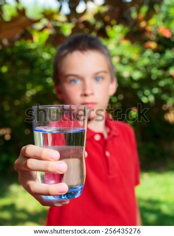 Boy holding glass of water outdoors - stock photo