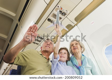 Boy holding model airplane besides senior man and woman on airplane - stock photo