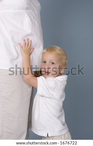 Boy holding pregnant mother stomach