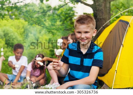 Boy holding stick with marshmallows during camping - stock photo