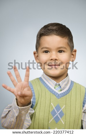 Boy holding up four fingers - stock photo