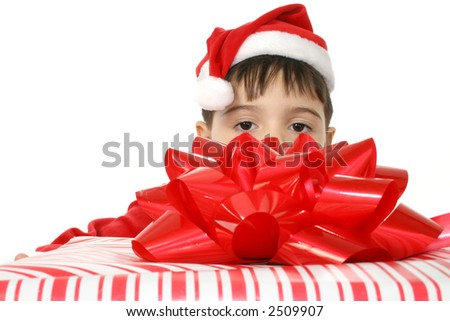 Boy holding very large red and white wrapped Christmas gift.