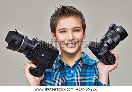 Boy holds the two photo cameras. Smiling caucasian boy  with dslr camera posing at studio over grey background