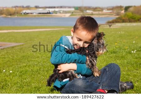 Boy hugging a dog - stock photo