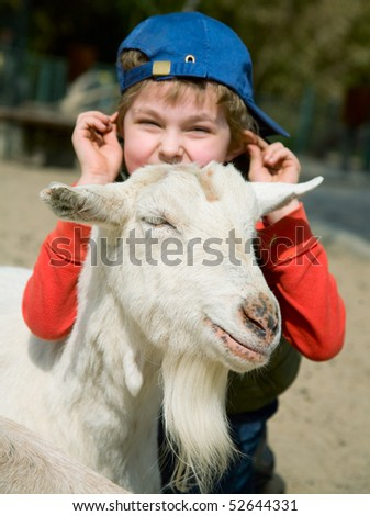 Boy hugging a goat on a platform for young - stock photo