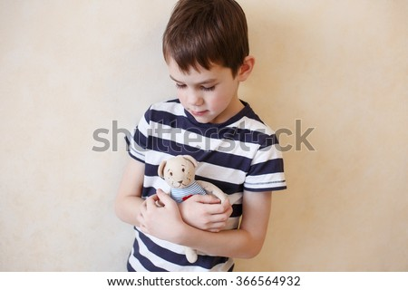 boy hugging a teddy bear. child with tenderness looks at the beloved the toy bear. concept children get older, a farewell to childhood - stock photo