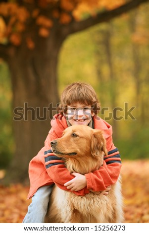 Boy Hugging Dog in the Fall - stock photo