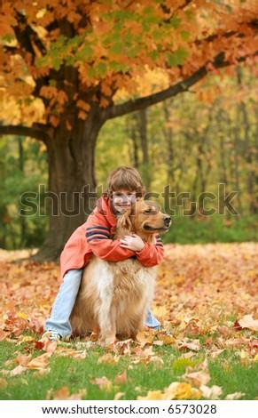 Boy Hugging Golden Retriever - stock photo
