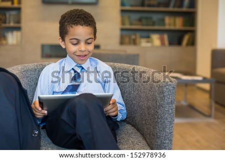 Boy in a business suit with the tablet sitting in a chair in a business center
