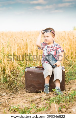 boy in a field with a tablet - stock photo
