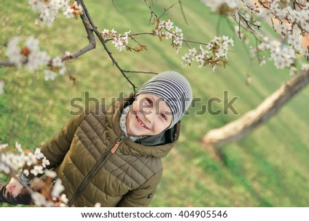 boy in a jacket and hat walking in the garden with flowering trees - stock photo