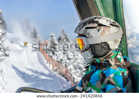boy in a mountain-skiing helmet and points is represented on the ski lift