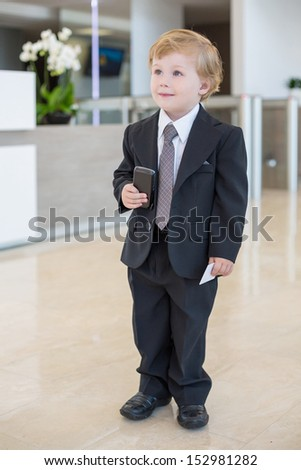 Boy in a suit with phone in hand in the business center - stock photo