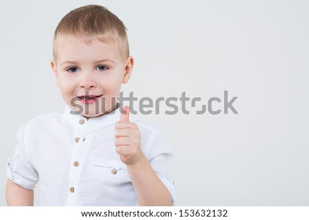 Boy in a white shirt making thumbs up in the studio
