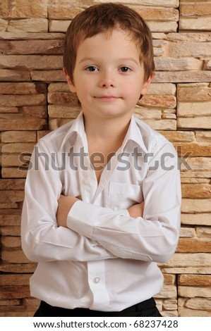 boy in a white shirt with his arms folded