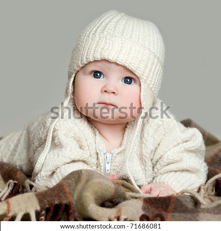 boy in a woolen cap on a warm plaid - stock photo