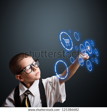 Boy in an adult business suit choosing shopping cart button - stock photo