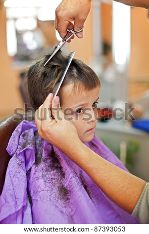 Boy in barbershop sad about loosing his hair - stock photo