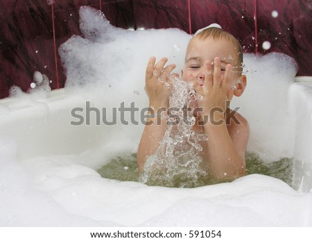 boy in bath with splash of water in hands