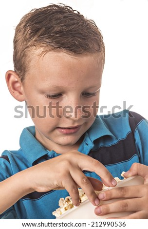 boy in blue shirt in studio eating popcorn