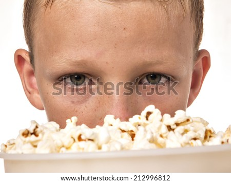 boy in blue shirt in studio eating popcorn - stock photo