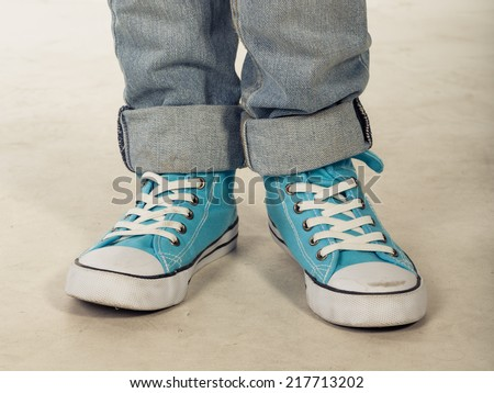 Boy in blue sneakers standing