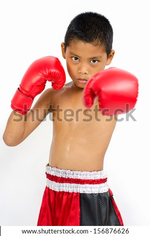 Boy in boxing gloves throwing some punches - stock photo