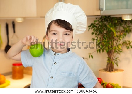 Boy in cap chef in the kitchen holds an apple - stock photo