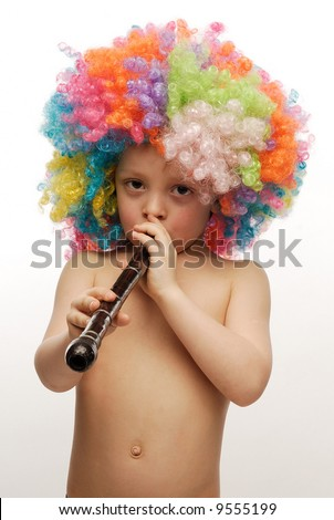 Boy in colorful bright wig playing a pipe - stock photo