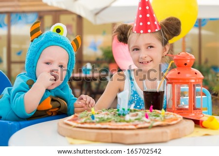 Boy in costumes of monsters and girl in festive cap having fun in a cafe with pizza - stock photo